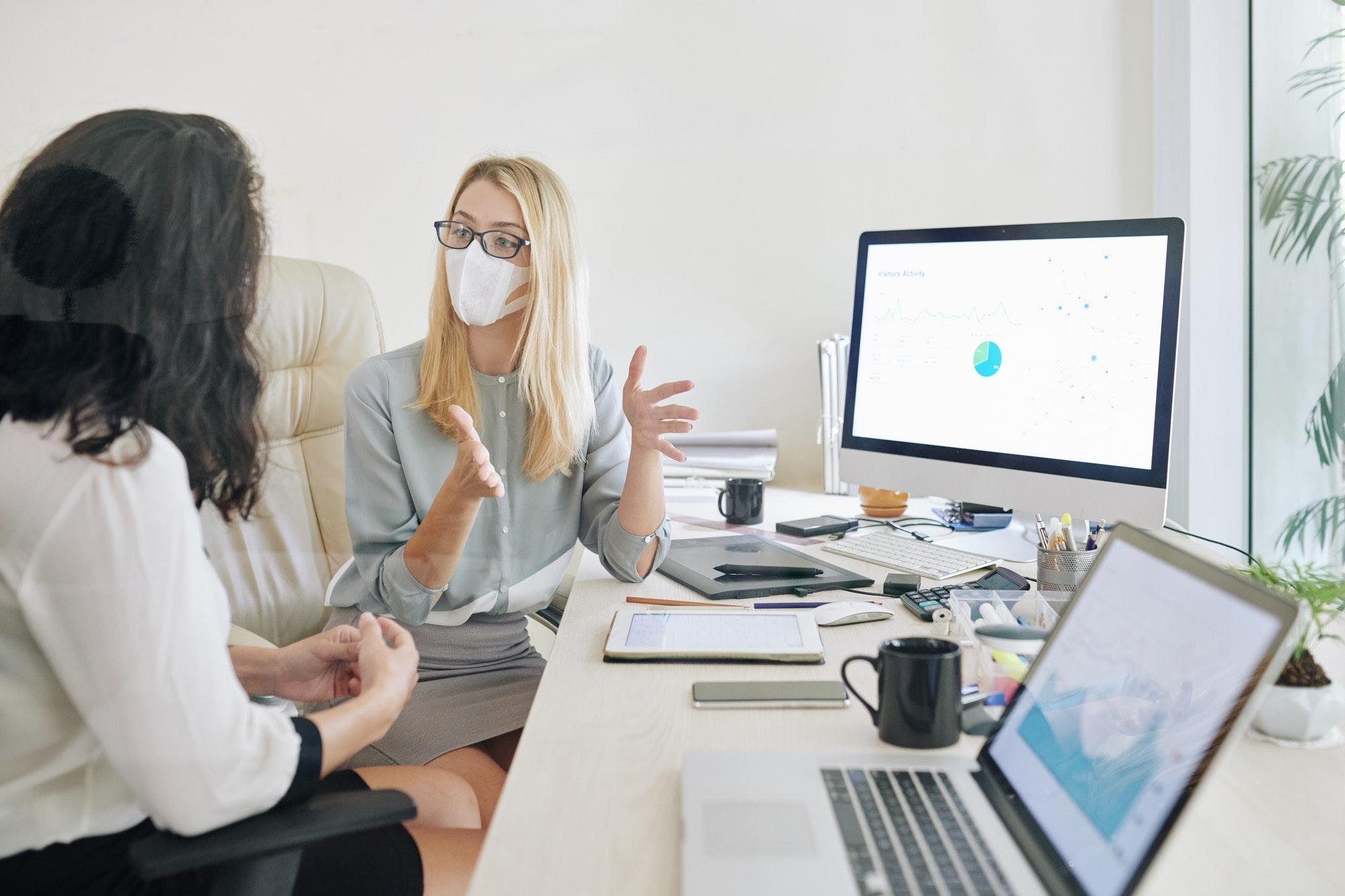 Businesswoman in medical mask explaining her idea