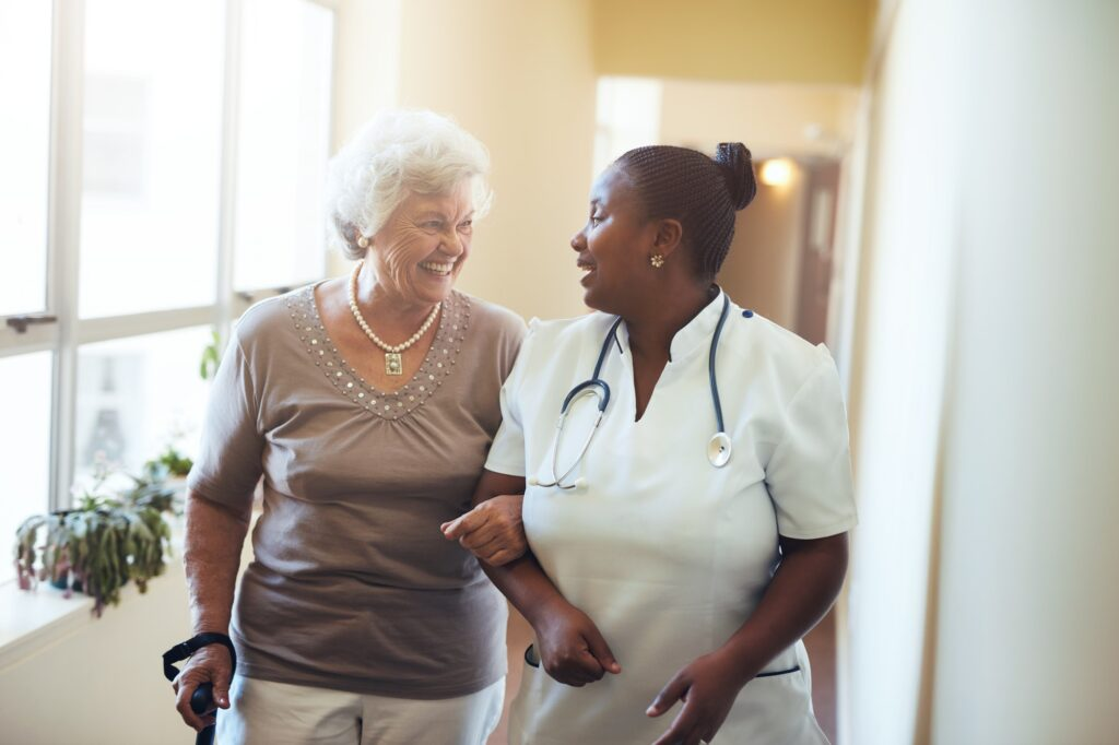Nurse assisting senior woman at nursing home